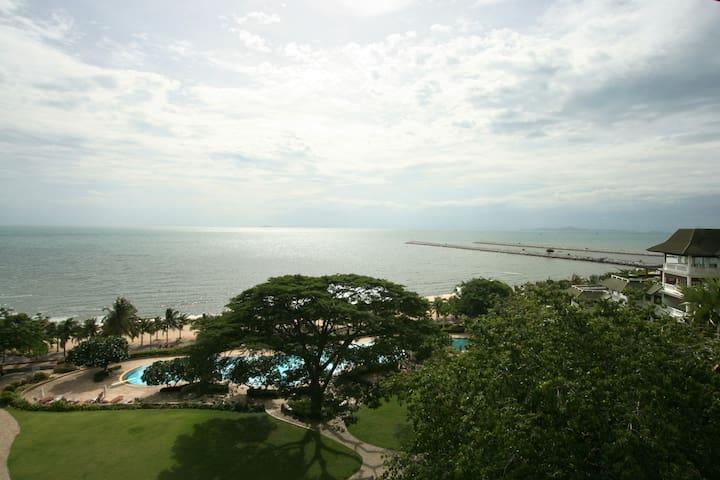 The view of ocean, swimming pool garden, and walking bridge from balcony (Rainy Season)