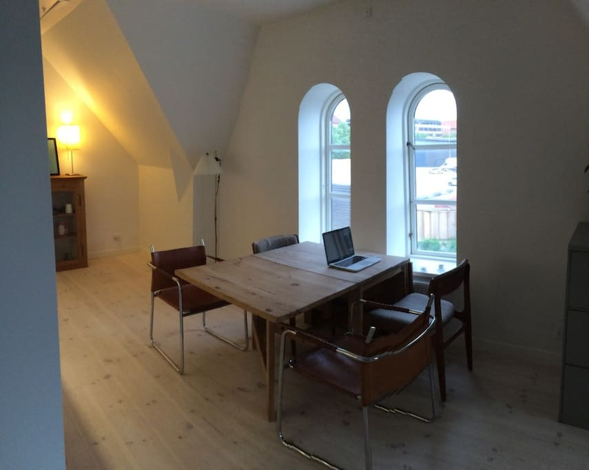 Sitting room, dining area and kitchen in one big loft style space with decorative rounded windows and original beams showing.