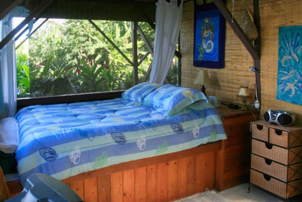 Queen bed with ocean and garden views