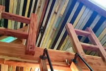Stout cedar newel posts and handrails make the upstairs loft safe and sound. Plumbing pipes on the ladder provide extra hand grips and a rustic utilitarian look. Our walls and ceilings are clad in multicolored ill-painted  beaded board salvaged from many old homes around Atlanta.