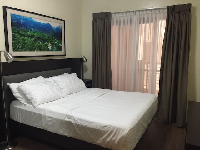 Room 1:This is the Master`s Bedroom. It has a queen sized bed, internet enabled TV(Netflix ready) ,medium sized closet , luggage rack and a sliding glass door to access the balcony .
