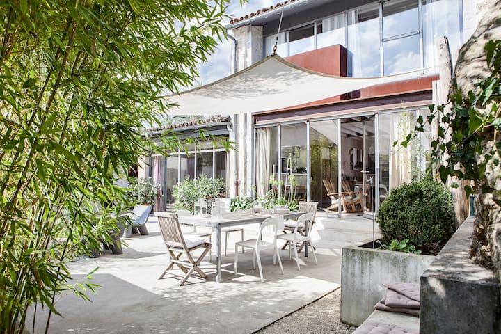 Maison atypique avec piscine et cheminée.