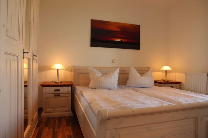 in der unteren Ebene ein Schlafzimmer mit großen Doppelbett und einem geräumigen Kleiderschrank