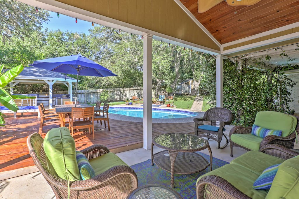 Relish in the backyard oasis that offers a pool, covered patio, outdoor seating, and an outdoor kitchen.