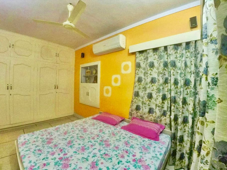 Room 1(AC): A calming Sun Orange colored room, comes with top notch O'General AC. It has a Wardrobe and a 5.1 Sony music system. This room is well lit with windows in two walls.