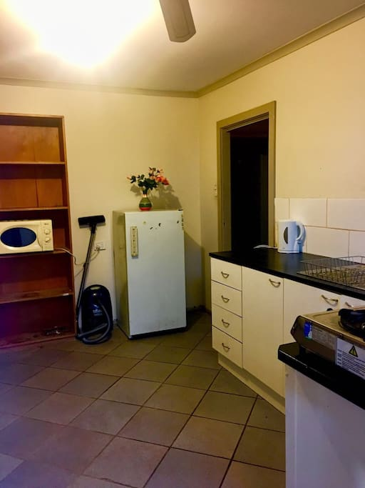 Kitchen with fridge, microwave, vacuum cleaner, hot water kettle, toaster and cooking gas for your convenience