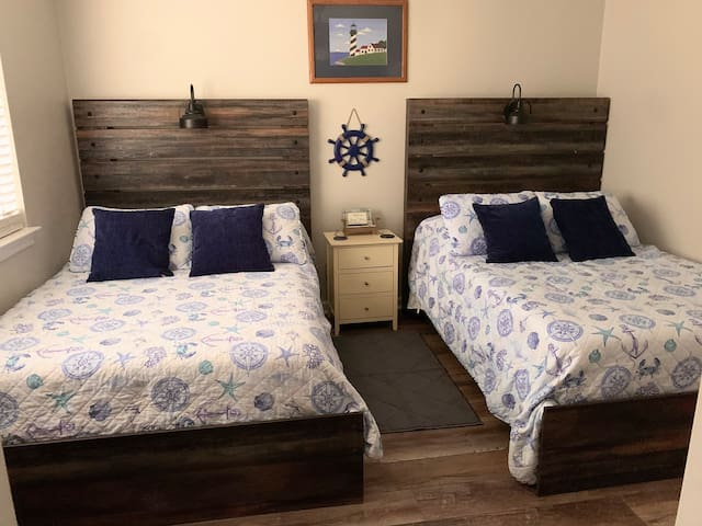 2 Full beds Lighthouse/Sea theme. Mounted tv, phone chargers for both sides.  Jack-n-Jill set up with shared bathroom. Bathroom has most needed toiletries.