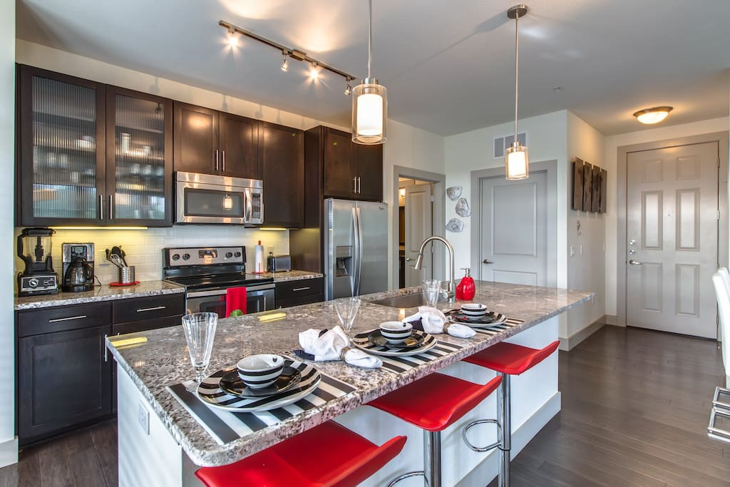 Stylish fully equipped kitchen with granite counters and stainless appliances