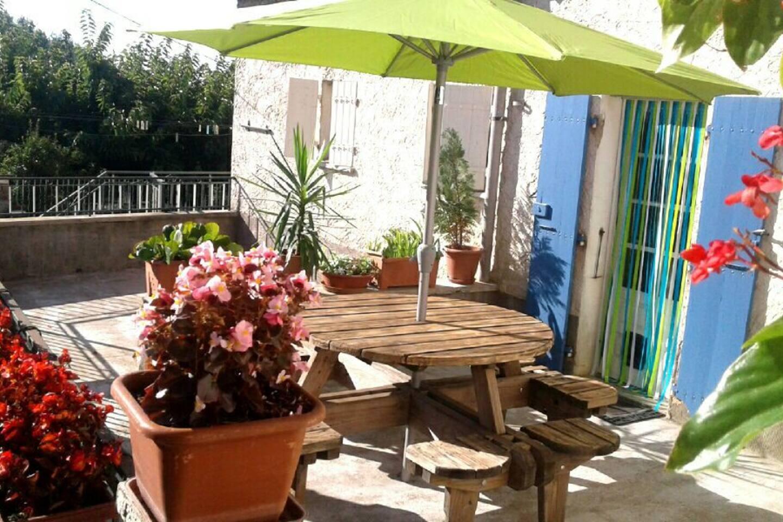 terrasse fleurie de 25 m2 privative avec table en bois.parasol,étandoir et barbecue