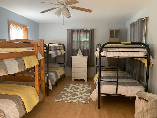 3 sets of bunk beds in bedroom 3 includes closet storage, dresser and overhead fan.