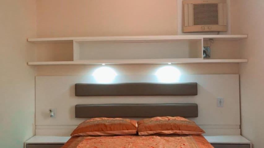 Cama de casal Queen; colchão de molas. Cabeceira e luzes de led para leitura; criados mudos com tomadas.