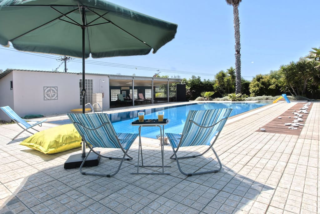 Outdoor swimming pool, relaxing area with chairs for sunbathing and view towards Taygetos mountain