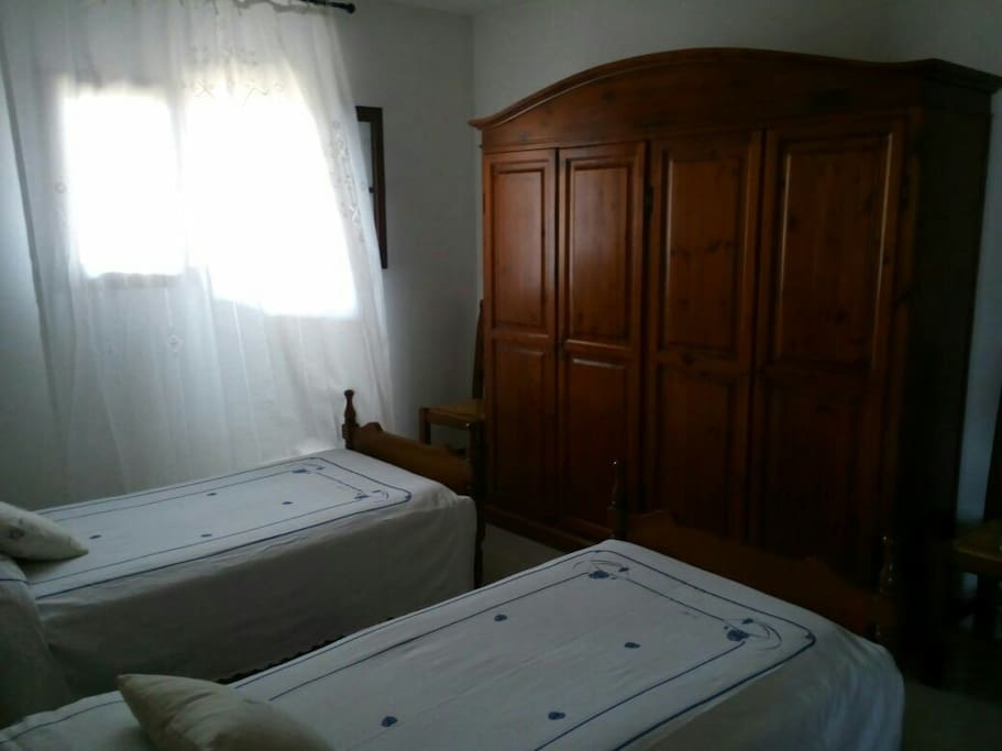 Small double bedroom with 2 single beds, wardrobe and couch.