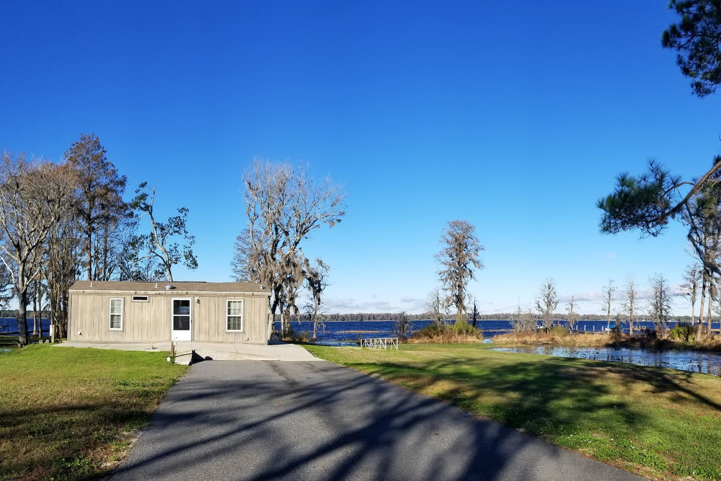 Cabin sitting above the lake & canal with long private drive.