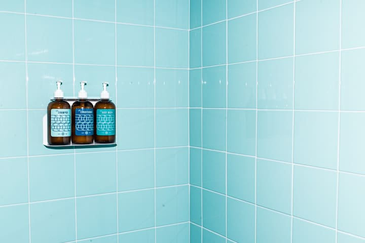 The blue shower tile compliments the purple room well.
