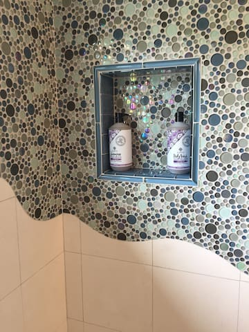 Large shower right outside of your room with inspiring design, filtered water, and natural toiletries.