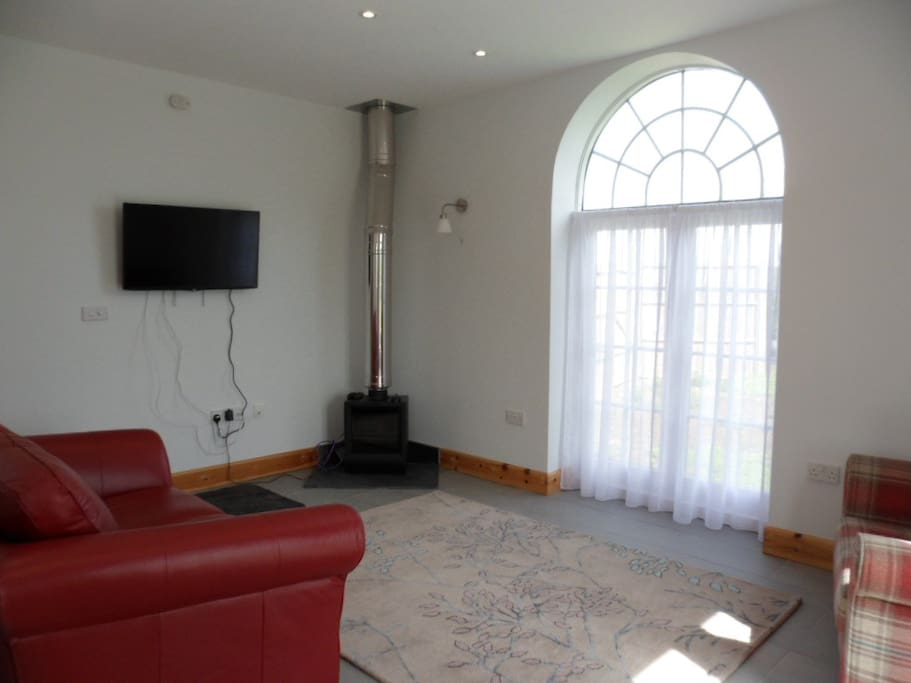 Reception area with multi-fuel stove, arched window, leather sofa, snuggle and arm chair and smart tv connected to the internet.  The downstairs accommodation has underfloor heating