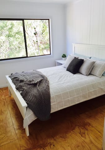 The back bedroom (white room) contains a queen sized bed and views of the surrounding bush land and national park.