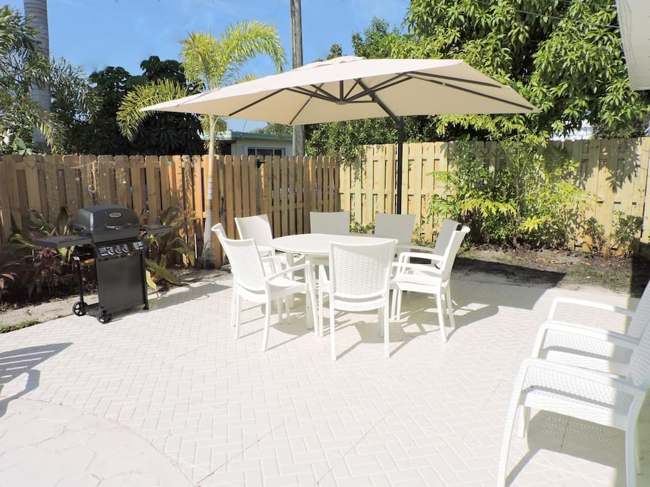 BEAUTIFUL HEATED POOL, DINING AND GRILLING AREA IN THE LUSHLY PLANTED TROPICAL BACKYARD WITH LOUNGING CHAIRS