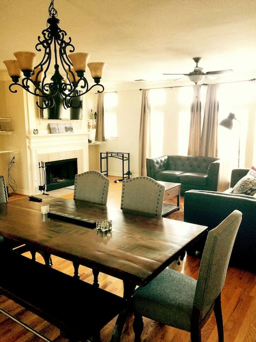 Living room area with fireplace and 65 Ultra high definition TV.  Dining room area includes rustic wood table with bench and 4 chairs