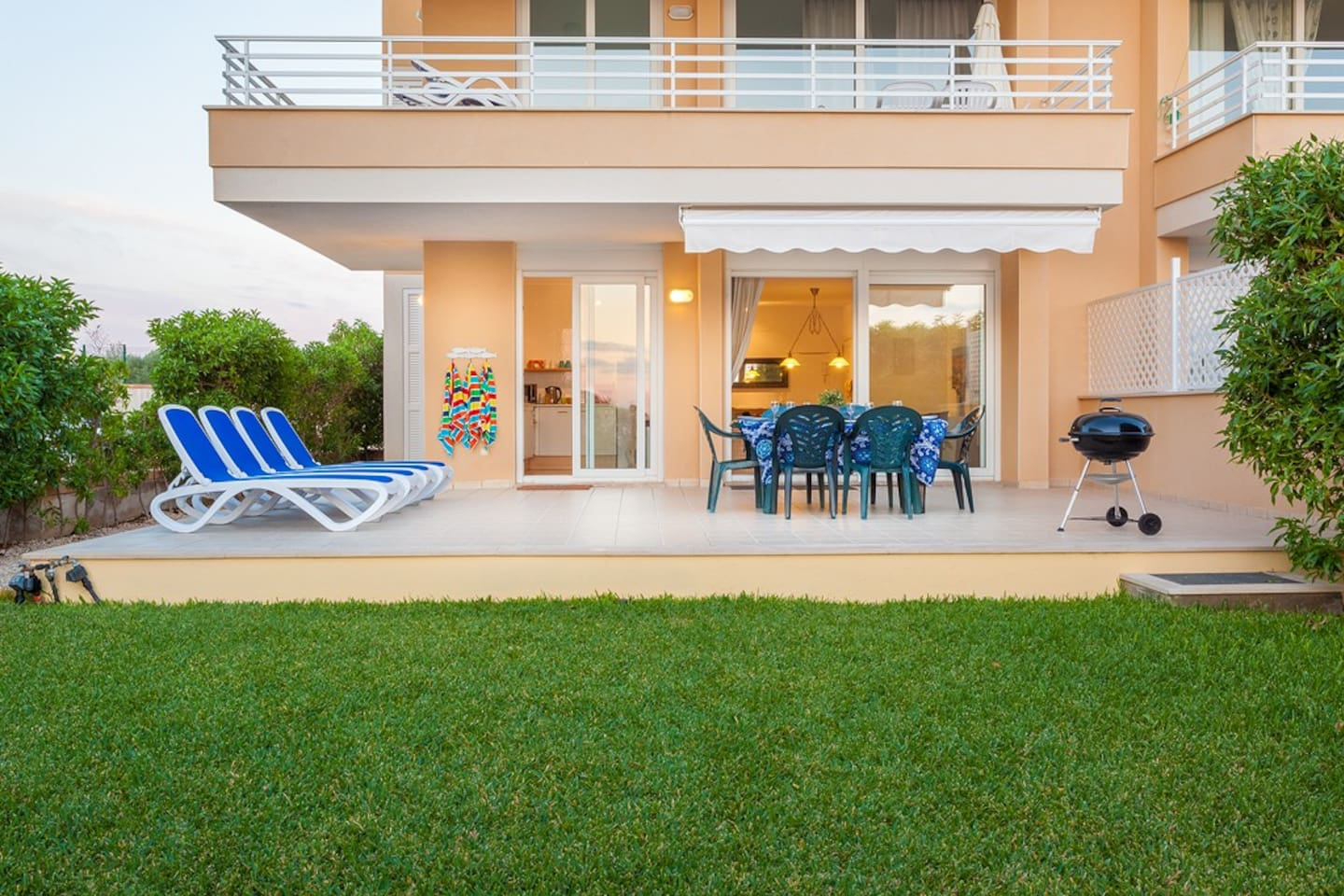 The spacious verandah leads onto a private garden with steps leading to the shared adult and children's swimming pool area.