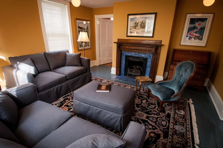 The living room, featuring an elegant blue tile and cast-iron fireplace.