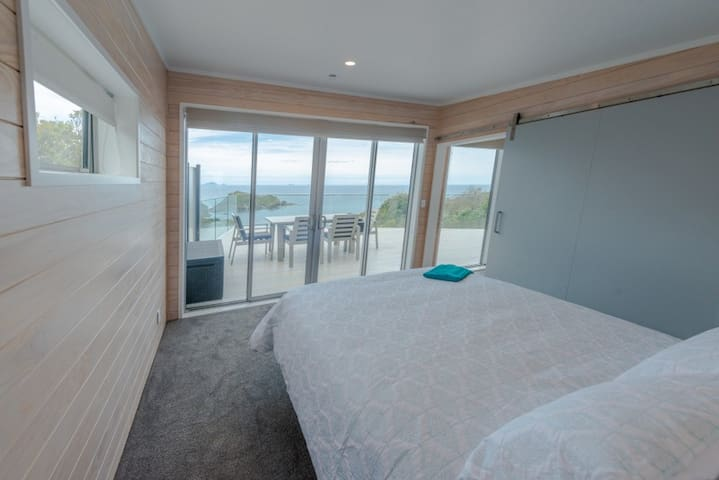 Bedroom with queen bed looking  out to beautiful  views