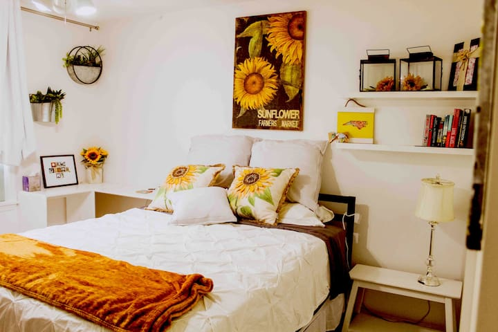 Sunflower room has a queen bed, closet space, dresser and TV