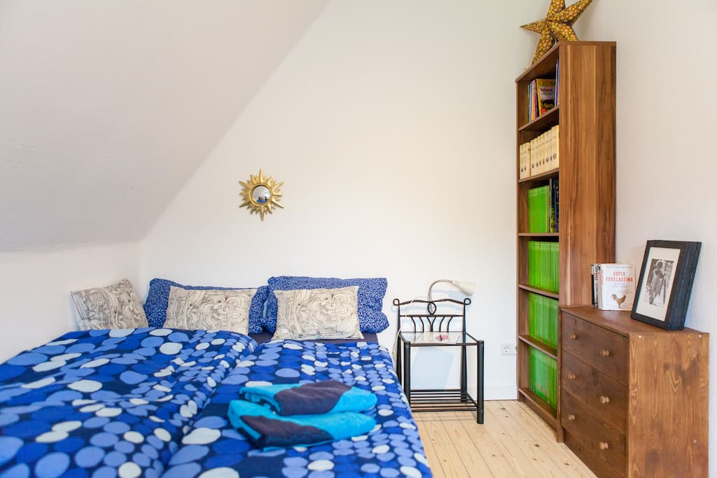 Dein Bett neben der kleinen Gästebibliothek