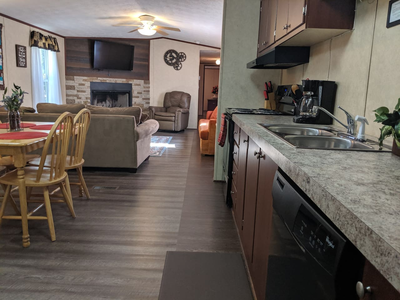 Spacious living area and kitchen with custom fireplace and flooring. Cozy, rustic, and beautifully decorated for your stay.