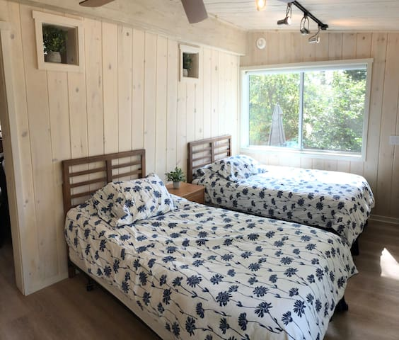 The Bedroom has two twin beds, an overhead ceiling fan, large windows with room darkening shades, ample closet space.