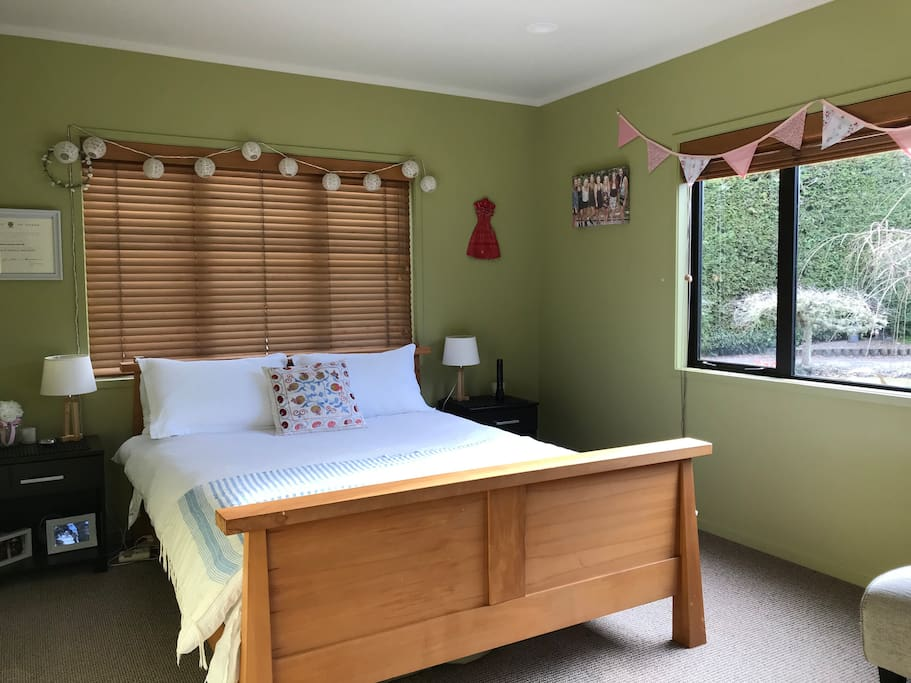 Main bedroom with queen bed and lovely garden views .
