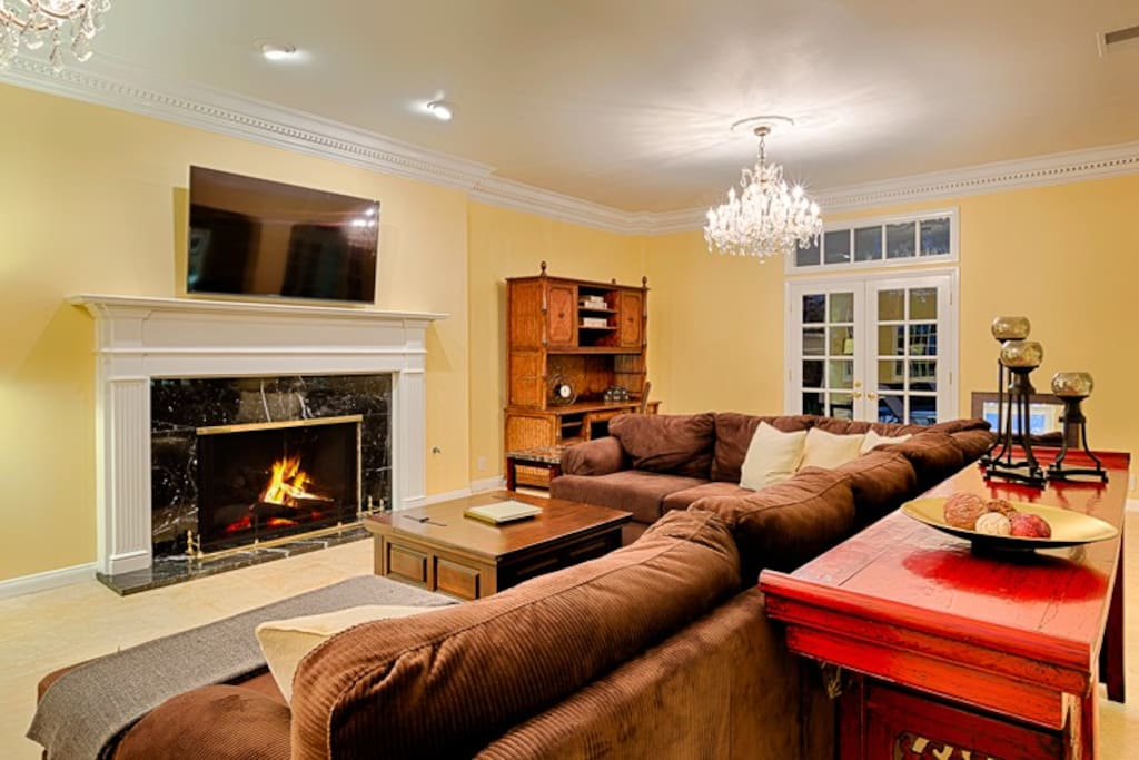 The living room features plush seating, a fireplace, and large flat screen TV.