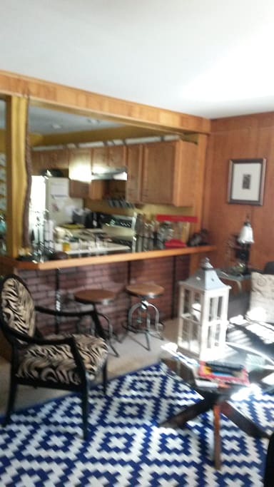 Living room looking into kitchen, two bar stools by counter