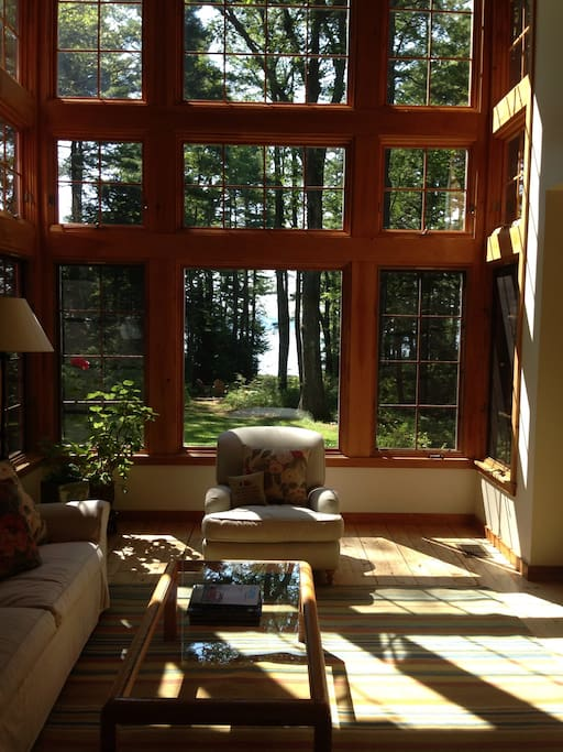 Living room has beautiful natural light filtered by trees in the summer.  Tall cathedral ceiling with a wall of windows facing south. Beautiful light throughout the day, in every season.