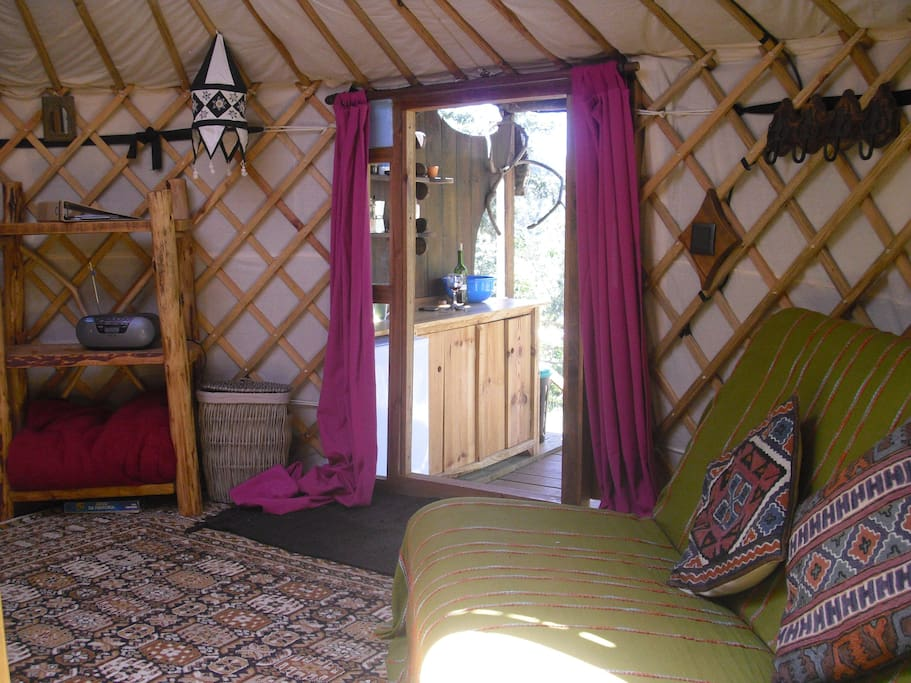 Woodland yurt interior with doorway to kitchen area and deck.