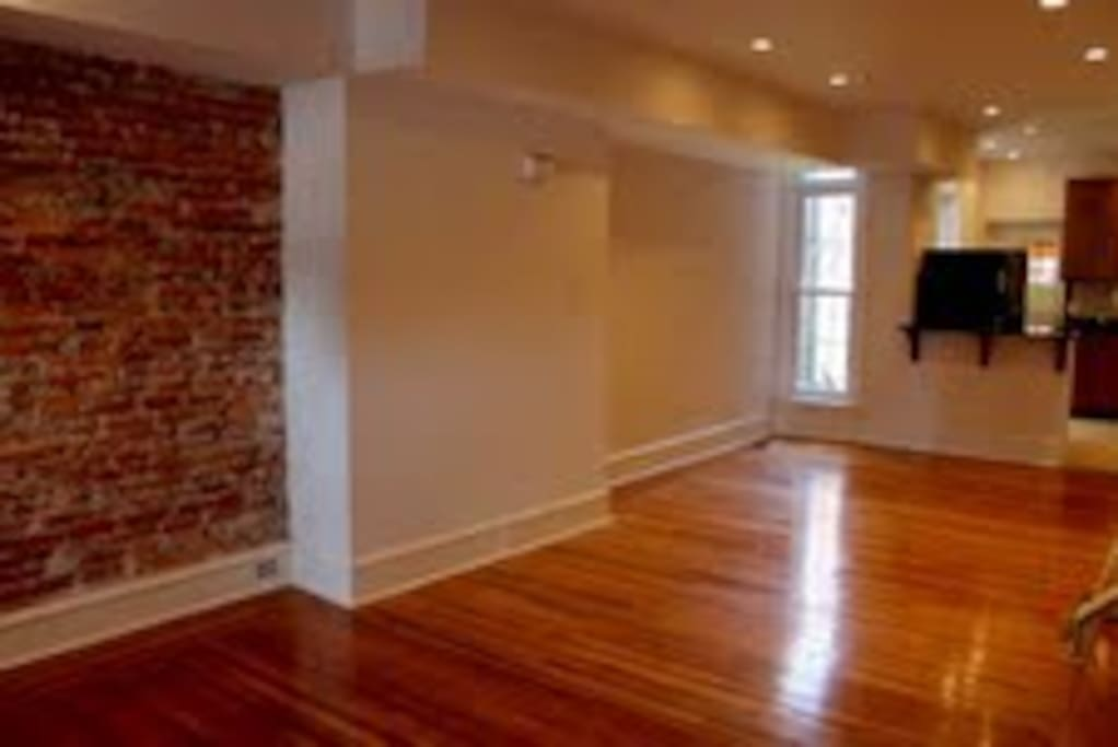 Check out the cool exposed brick with original hardwood floors and open floor plan