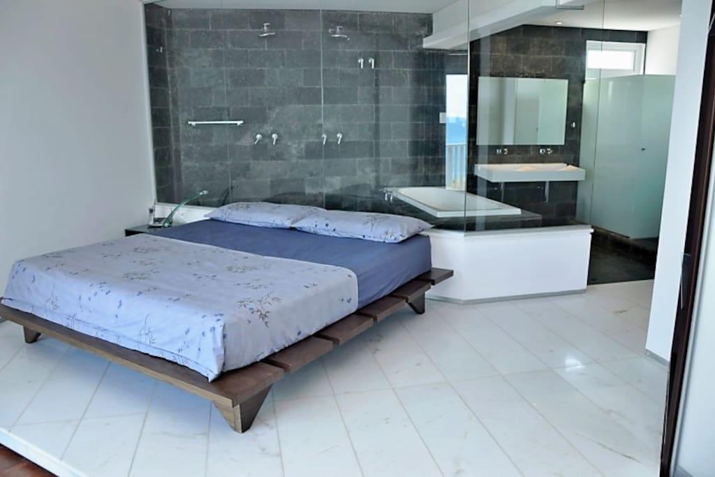 Master-suite, king-size platform bed, black slate bathroom, dual shower, soaking tub, dual sink, opaque glass-enclosed toilet