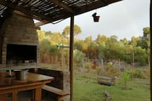 Terrace with braai, pizza oven, 4 seater table, sink with cold water, drop down sheets for the cooler nights, beautiful view over a forest