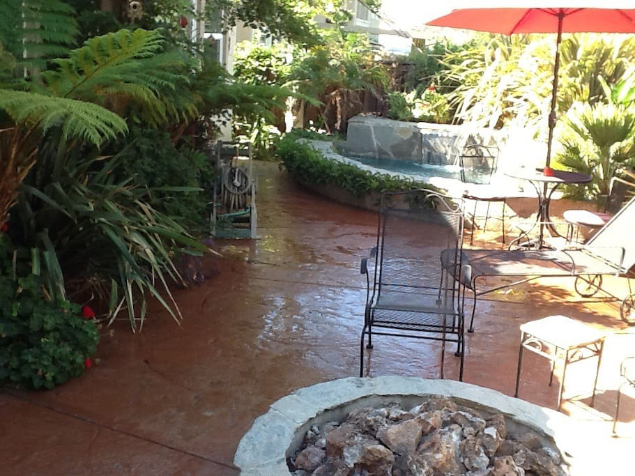 Tropical back patio with waterfall spa, bistro table to enjoy breakfast or warm up around fire pit in the evening