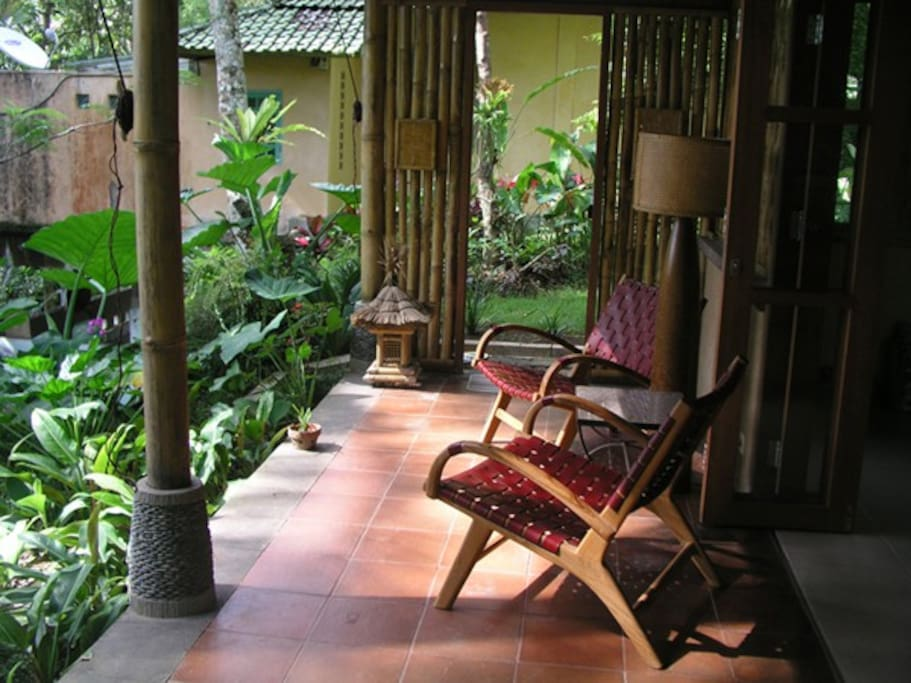 Ubud Contemporary Eco Bali Lumbung - red leather chairs looking out to the eastern rice fields