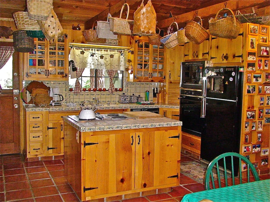 Kitchen and rear wall, with dutch door to rear deck and hot tub area beyond, overlooked by kitchen window.  Farm table dining to the right, and real wood burning brick wood fireplace to the left, and wood paneled beamed cathedral ceiling above..