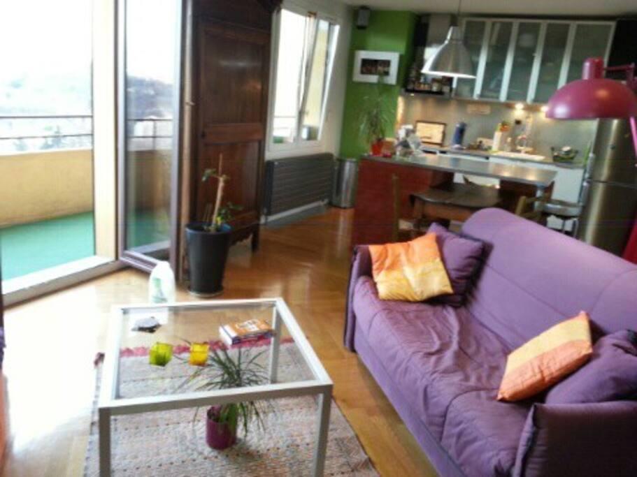 Pièce à vivre avec salon et cuisine intégrée donnant sur balcon.