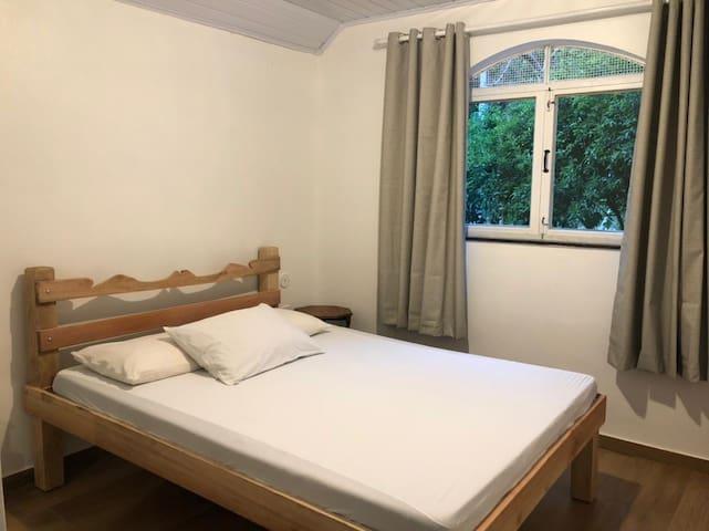 Suíte 1 com uma cama de casal e um colchão de solteiro e um banheiro com cortina no box para acessibilidade de cadeirante