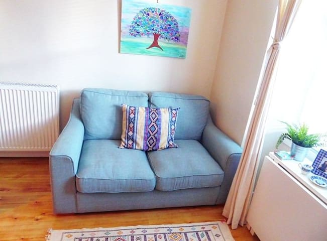 the comfiest couch you'll ever sit on, next to a beautiful painting made by my very talented mother!