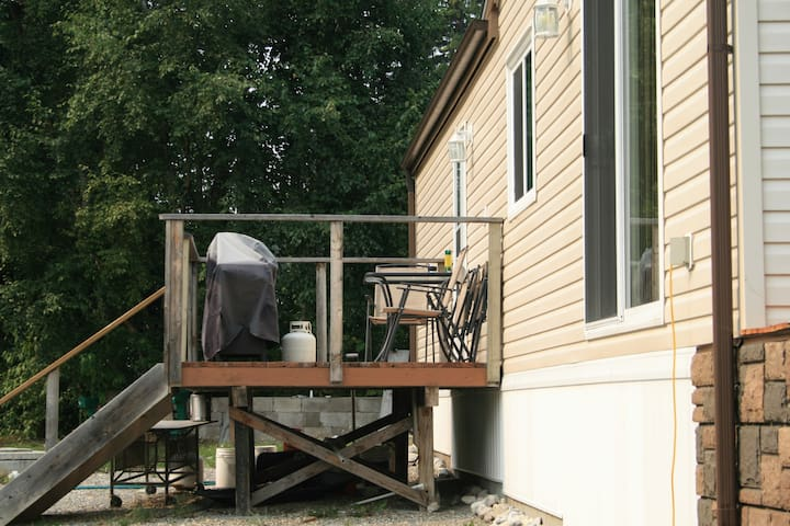 small deck off main enterance with  BBQ and outside dinning area