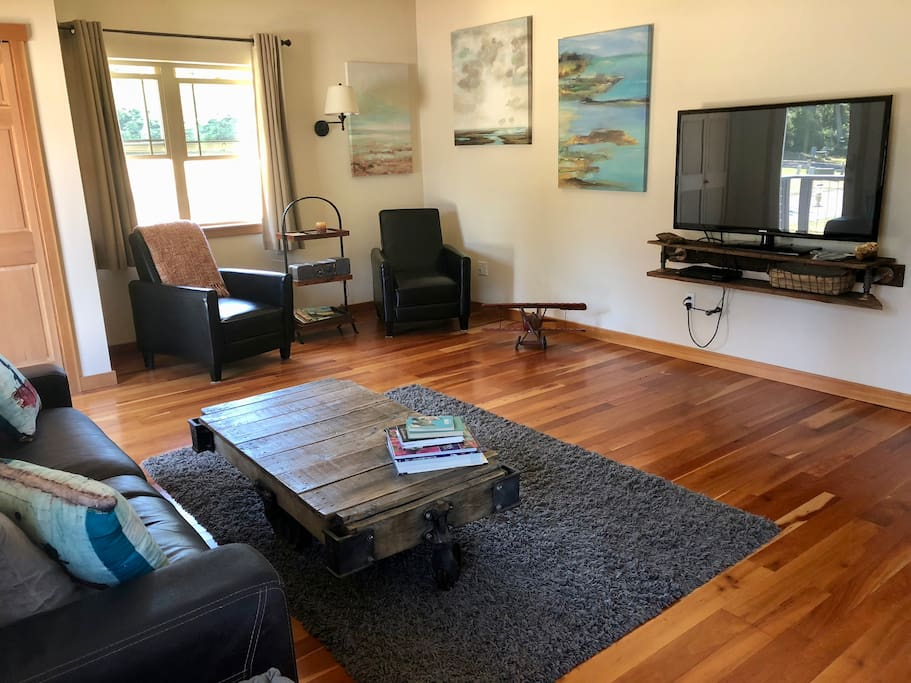 Living room features leather sofa, recliners, big screen tv with DVD player, assorted card and board games, and a view of the Mt. Constitution foothills
