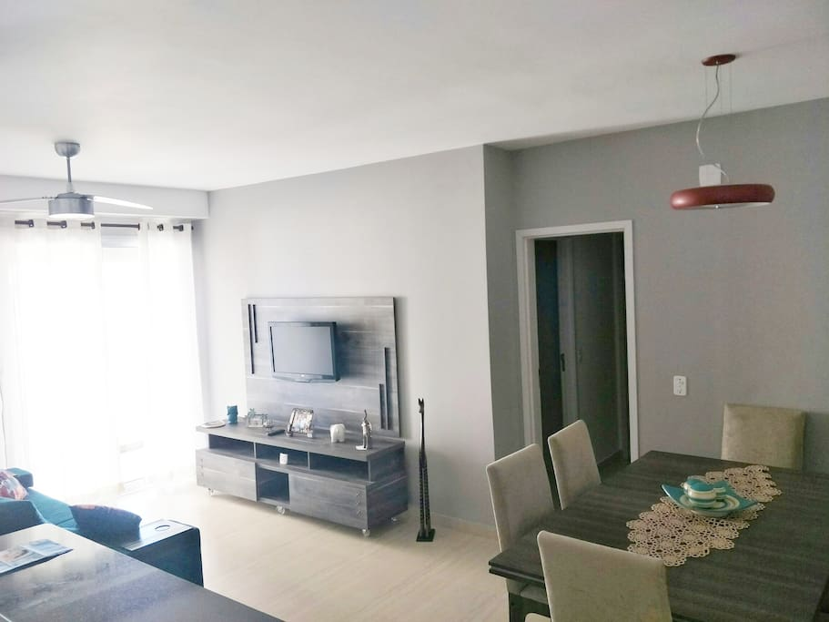 Sala de TV com tela plana e canais abertos,  equipada com sofá retrátil  e ventilador de teto.