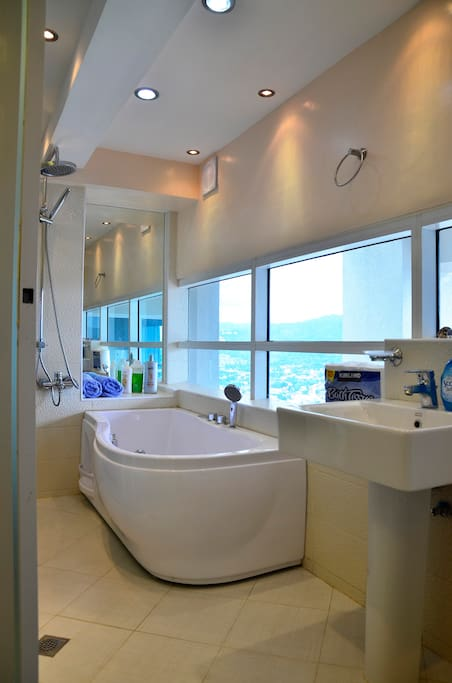 A Shower and a Jacuzzi with an unobstructed view of the mountain and the city.