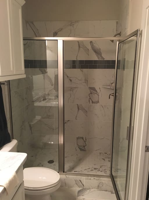 Marble-lined walk in shower.